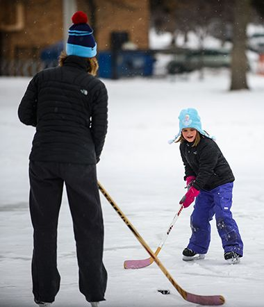 Family learning Hockey in the Winter on Ice Rink