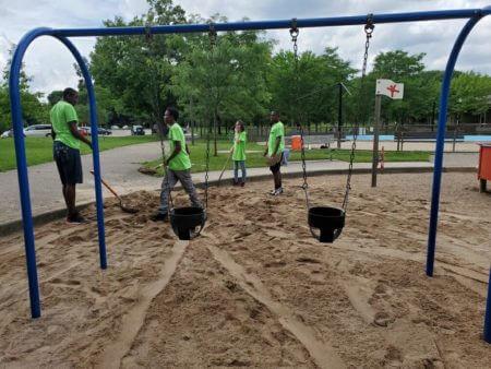 Teen Teamworks members doing playground maintenance.